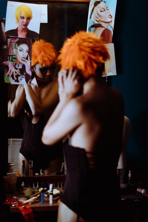 Back view bizarre female in black bodysuit putting on bright orange wig against mirror in dressing room