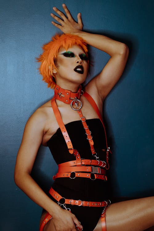 Provocative woman with orange hair in bodysuit standing alluringly