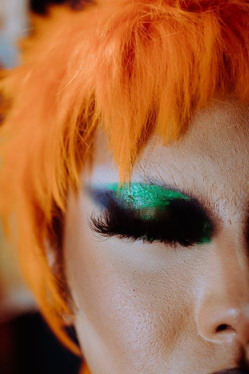 Crop woman with artistic makeup wearing orange wig