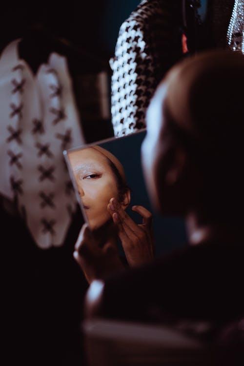 Crop androgynous woman applying skin foundation in dark room