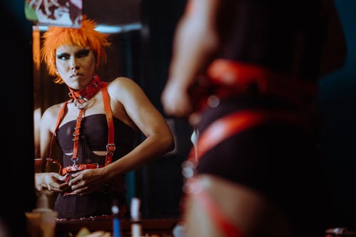 Crop informal female with funky makeup and orange hair wearing black bodysuit and putting on leather BDSM harness while looking in mirror