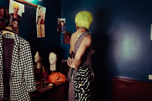 Faceless woman with green hair putting on weird dress