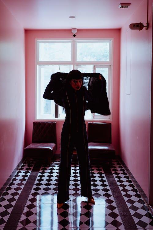 Informal funky woman in black suit standing in hallway
