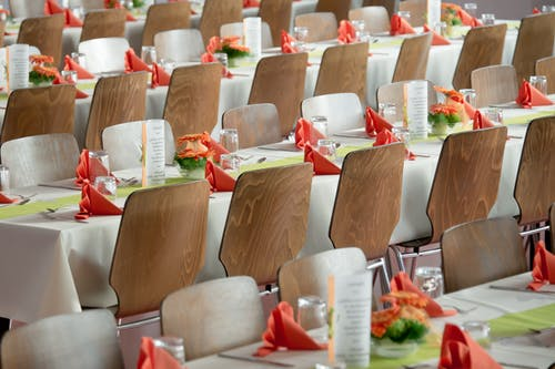 Long Tables With White Cloths and Brown Chairs Formal Setting