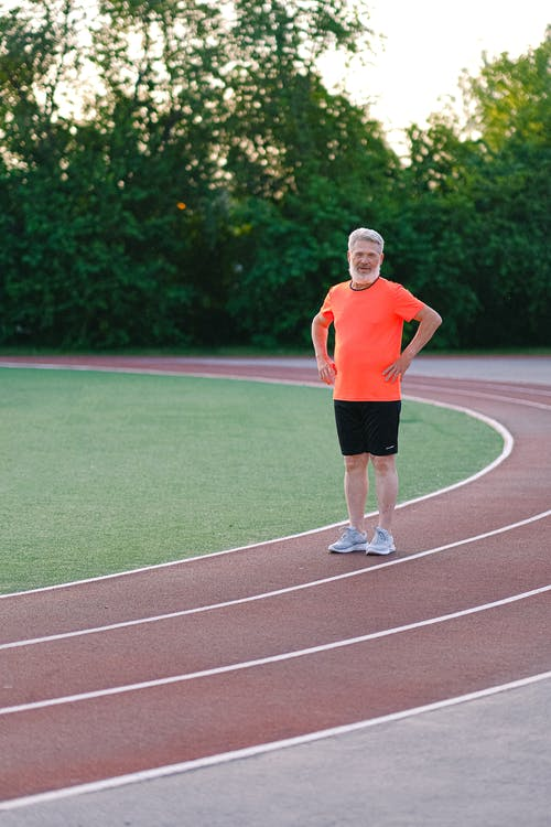 Senior man in sportswear on stadium track
