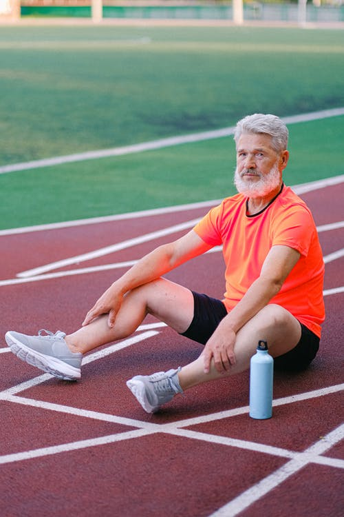 Elderly man resting on track in stadium
