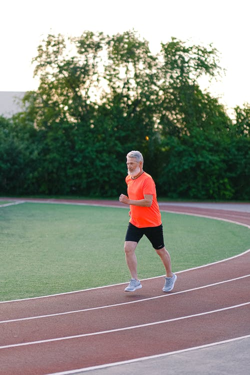Full body of elderly male jogging in stadium surrounded with lush green bushes