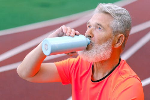 Elderly male with gray beard drinking liquid from thermos while resting after training on blurred background of racetrack