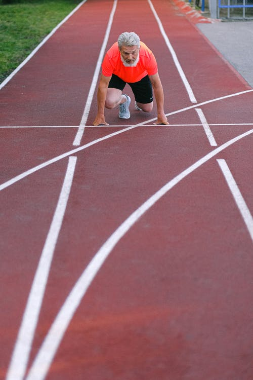 From above of confident elderly male starting for sprint on racetrack in stadium