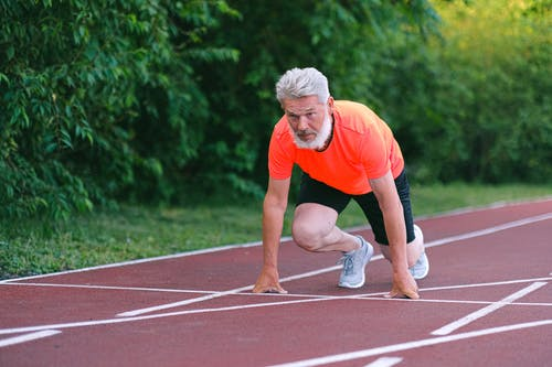 Serious strong elderly man starting for run in racetrack