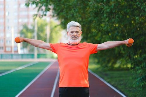Sporty elderly man training with dumbbells