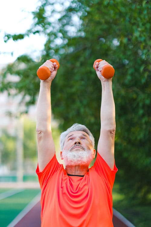 Senior man in sportswear doing exercises with dumbbells on stadium in sunny day