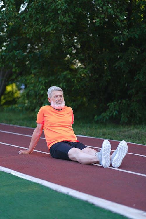 Senior man in sportswear sitting on stadium