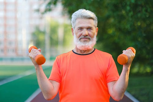 Smiling elderly man training with dumbbells on stadium and looking at camera in sunny day