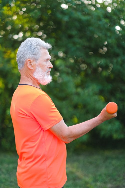 Side view of active senior man in bright sportswear training biceps with dumbbells in park in daytime