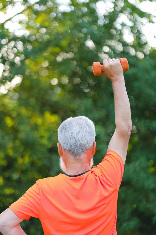 Strong aged sportsman training with dumbbells