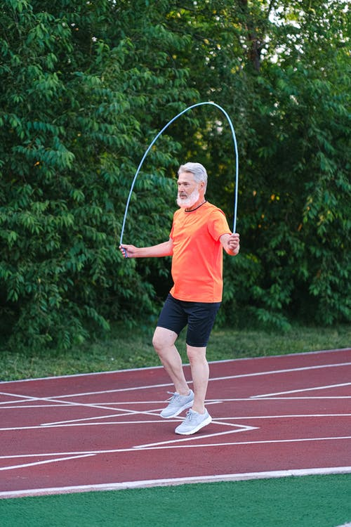 Senior sportsman training with jump rope on stadium