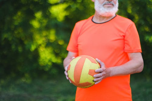 Crop unrecognizable senior man in sportswear holding ball during workout on street in daytime