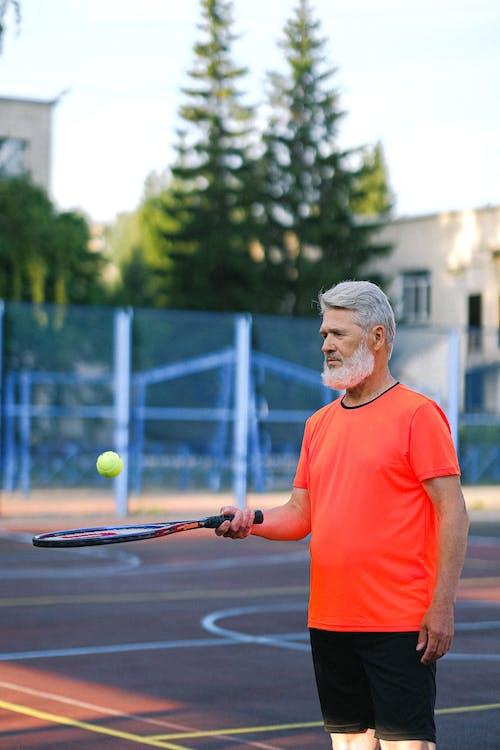 Senior man playing tennis on court