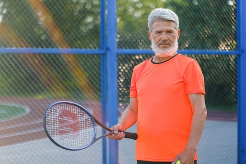 Focused senior sportsman in sportswear standing with racket while playing tennis on sports ground in sunny day