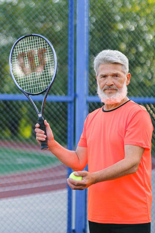Concentrated aged sportsman playing tennis on sports ground