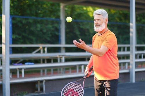 Focused elderly man playing tennis on street