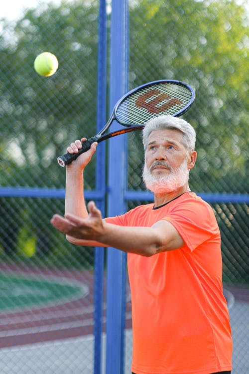 Serious aged sportsman in sportswear standing with raised hand with racket and throwing ball while playing tennis on sports ground in daytime