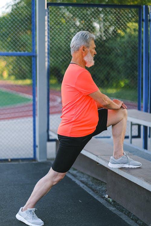 Senior sportsman stretching before training on street