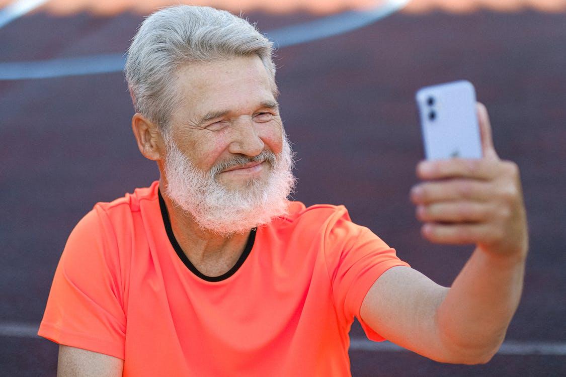 Senior Man in Orange Crew Neck T-shirt Holding a Smartphone