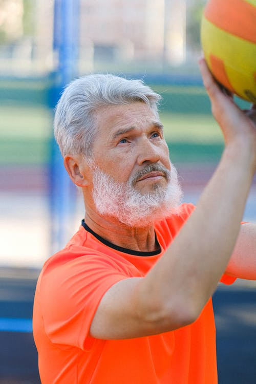 Mature man playing volleyball on sports court