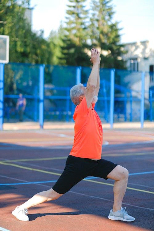 Senior Man in Orange Shirt and Black Pants Doing Yoga