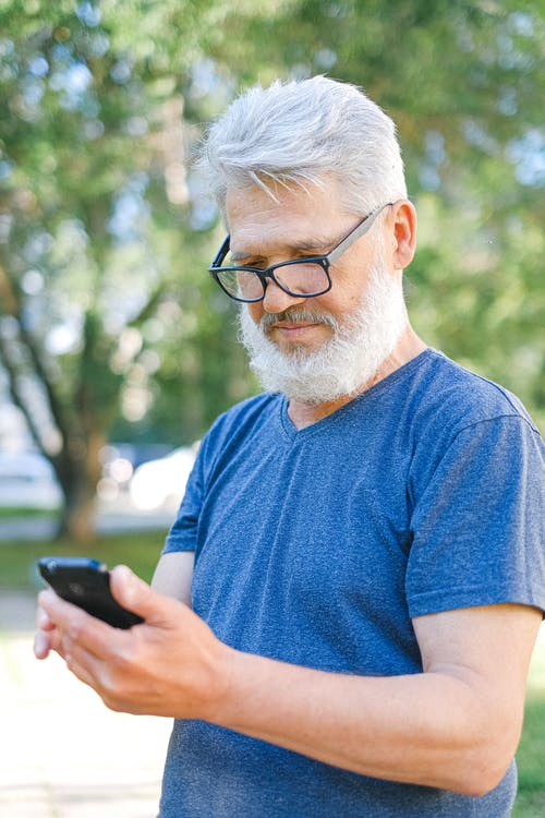 Senior Man in Blue T-shirt Holding a Smartphone