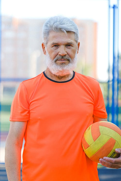 Confident elderly male with gray hair and stylish beard in sportswear holding ball during training on stadium