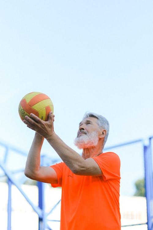 Elderly man playing volleyball on stadium