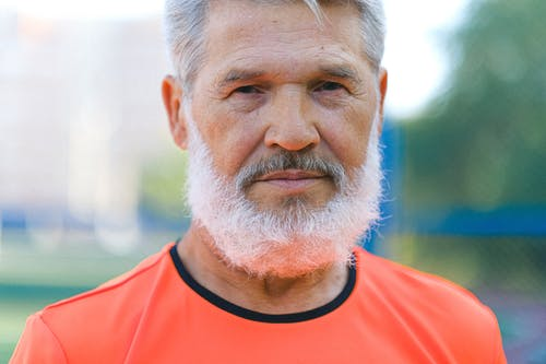 Crop senior male with gray hair and beard in casual t shirt standing in nature and looking at camera