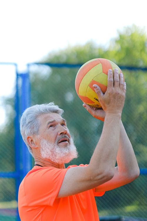 Concentrated man playing volleyball on sports ground