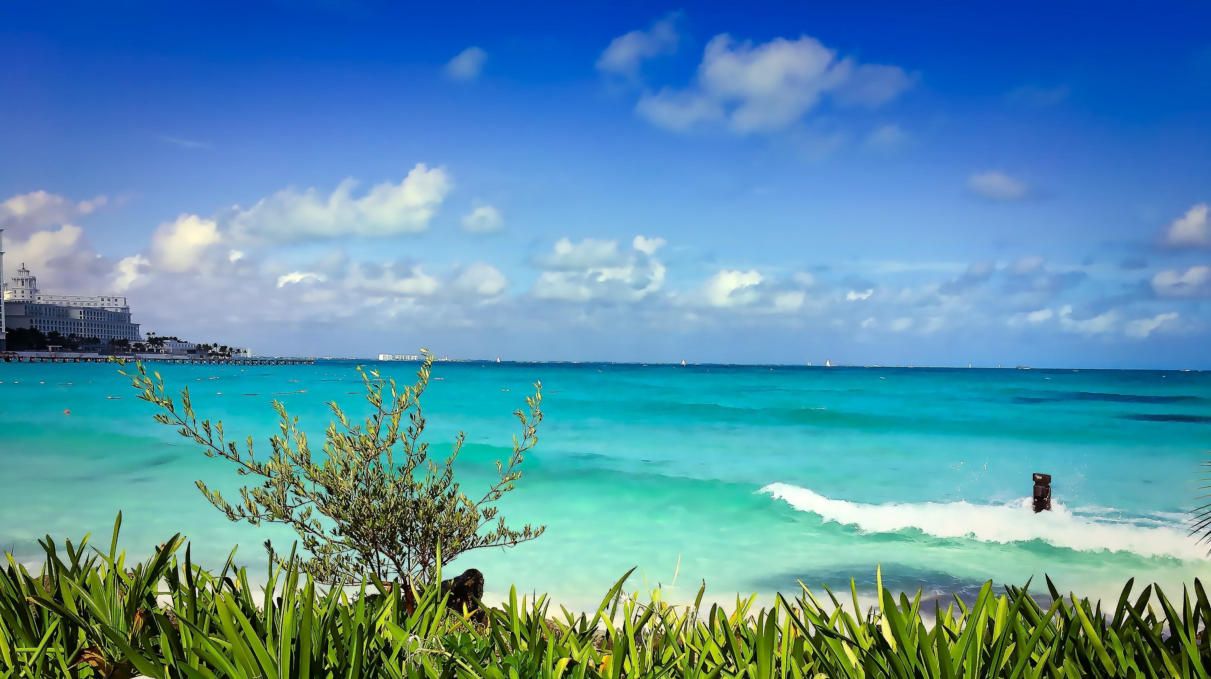 White Beach Shoreline Near Gray Rocks Under Blue Sky
