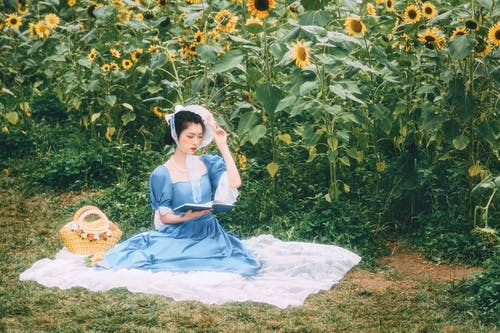 Girl in Blue Dress Sitting on White Textile Surrounded by Green Plants
