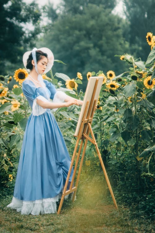 Woman in Blue Dress Holding Brown Wooden Ladder