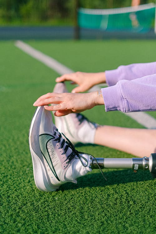 Crop unrecognizable female athlete with leg prosthesis doing stretching exercises while training on green court