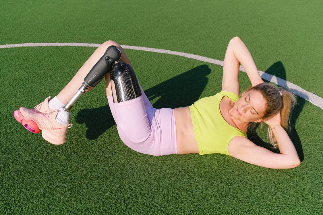 Full body of strong female athlete in sportswear with artificial limb doing abs exercises on sports ground