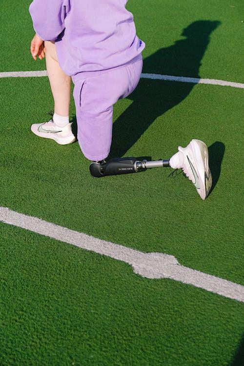 Crop woman with leg prosthesis training on stadium