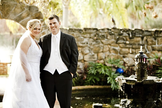 Man and Woman in Their Wedding Outfit With Brown Wall in the Background Near Fountain and Pond during Daytime