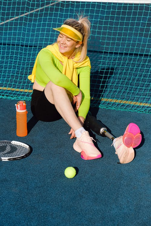 Woman in Green Long Sleeve Shirt and Black Pants Sitting on Tennis Court