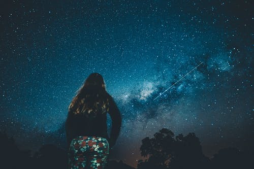 Unrecognizable woman admiring starry sky at night