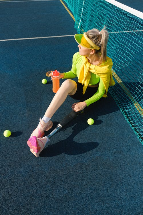 Woman in Yellow T-shirt and Black Shorts Sitting on Tennis Court