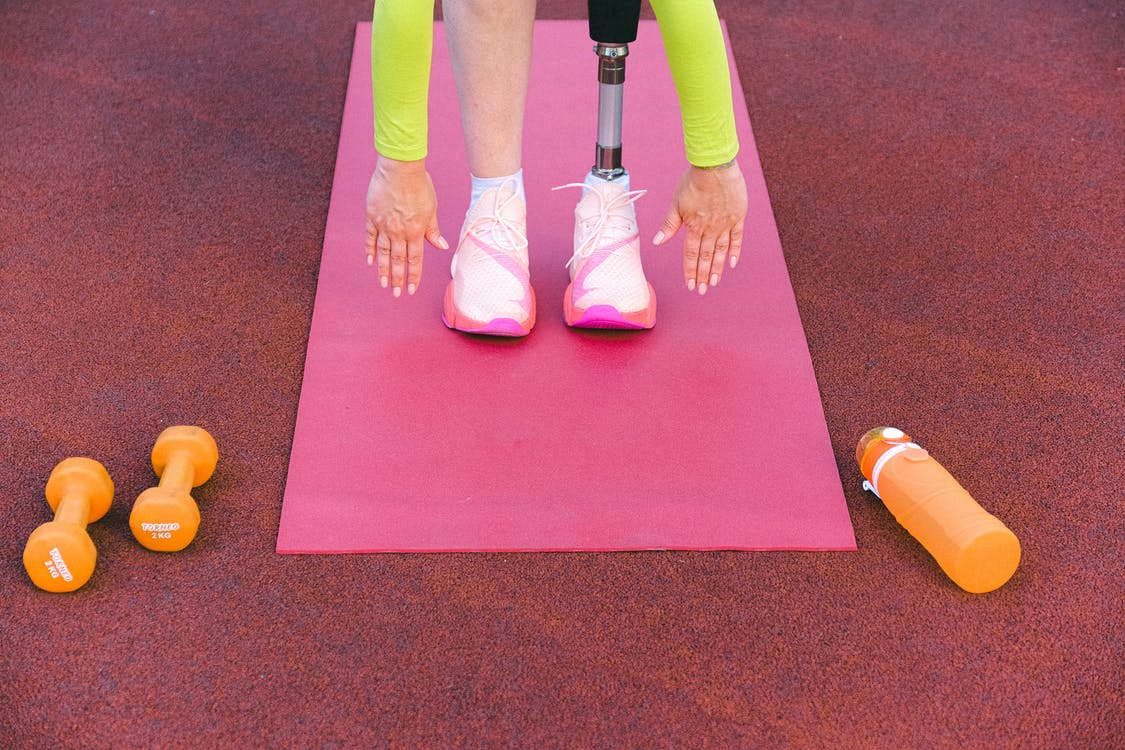 Unrecognizable female athlete with leg prosthesis bending forward and stretching while trying ti touch ground during training on sports ground with dumbbells
