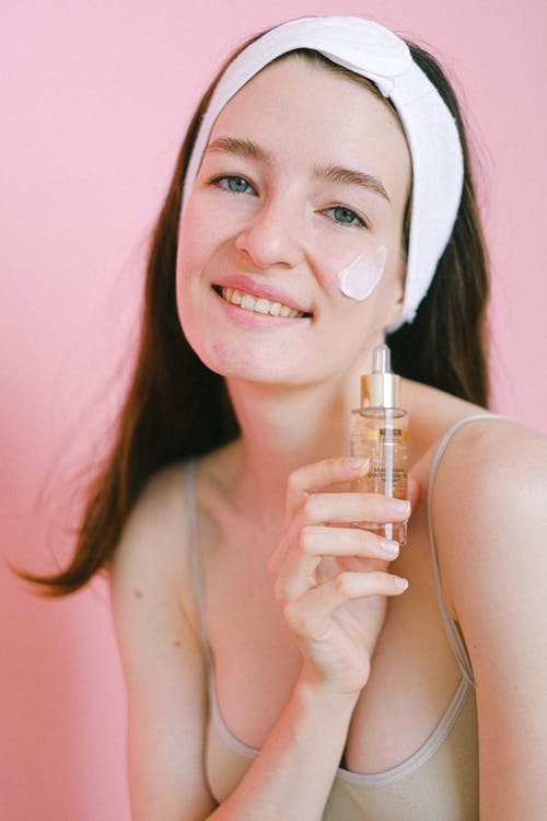 Happy woman with bottle of lotion
