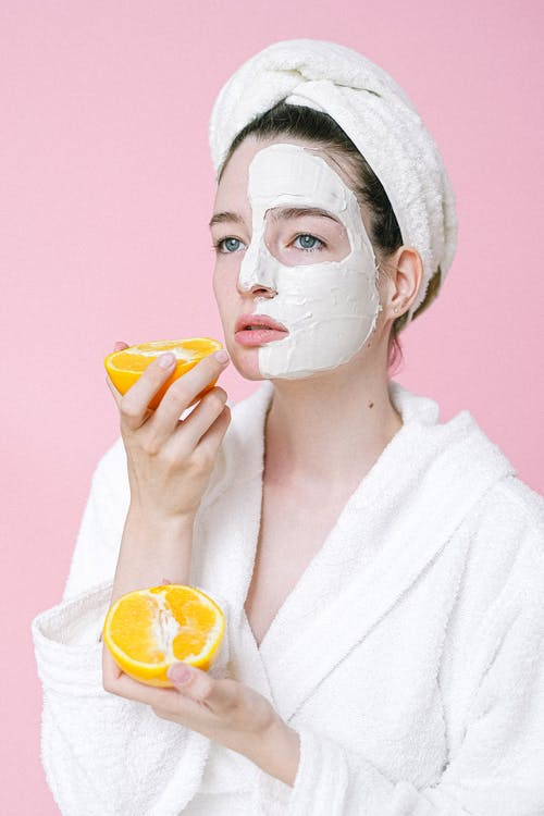 Dreamy female with oranges and mask on face