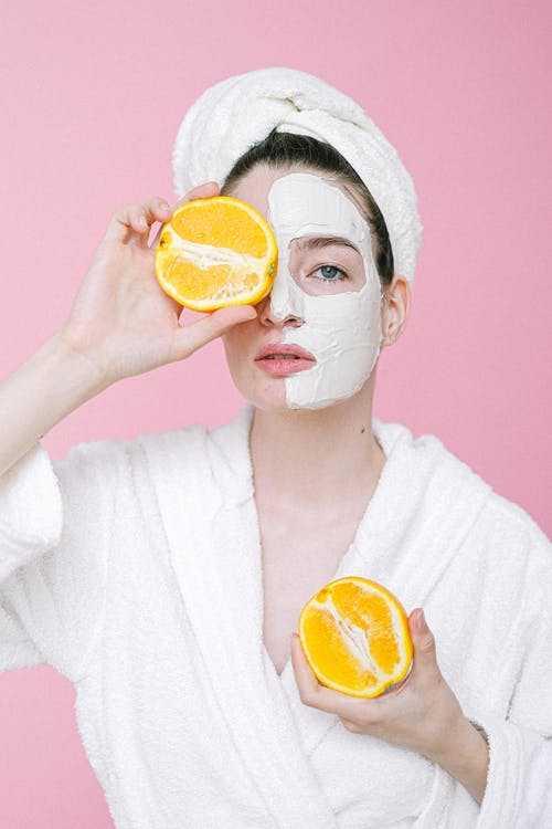 Calm female with towel on head and facial mask on face looking at camera while standing on pink background and covering eye with half of orange